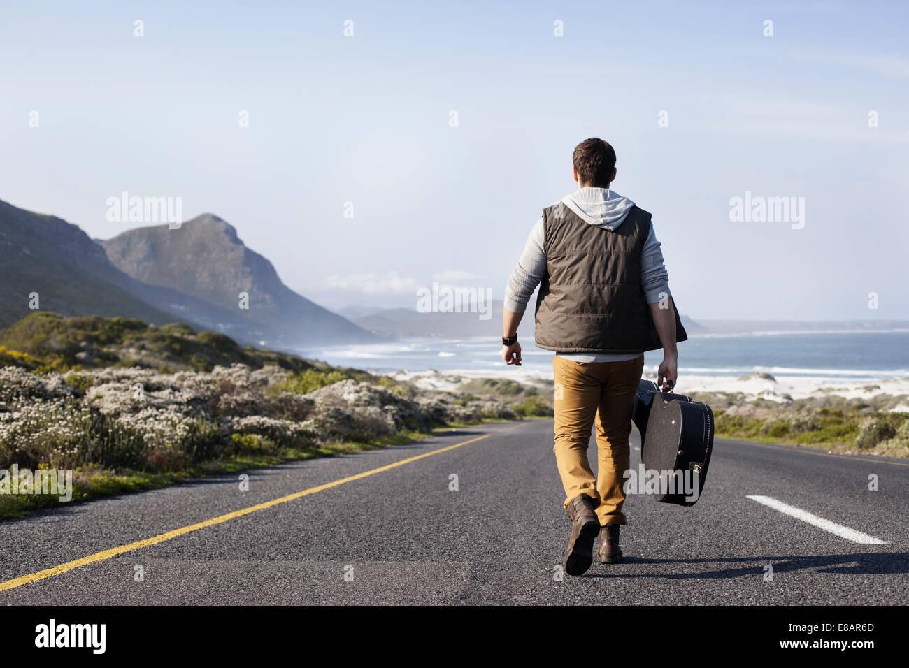 Vista posteriore del giovane con chitarra caso camminando sulla strada costiera, Cape Town, Western Cape, Sud Africa Immagini Stock