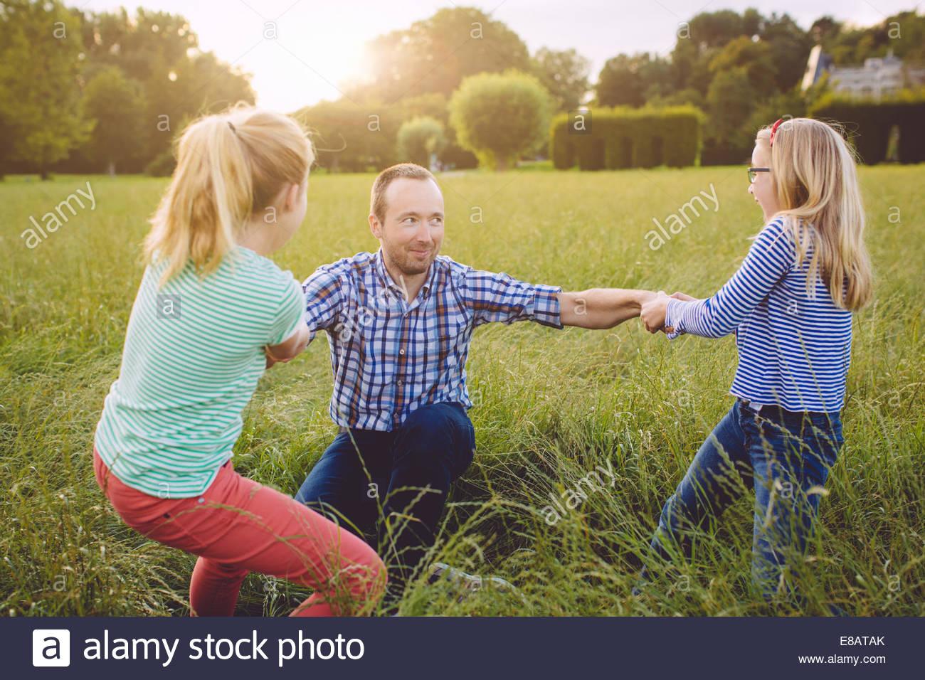 Due ragazze tirando padre fino dal suolo Immagini Stock