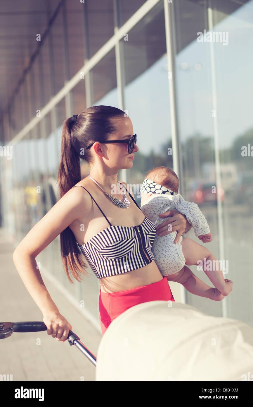 Moda la madre e il bambino nelle braccia Immagini Stock