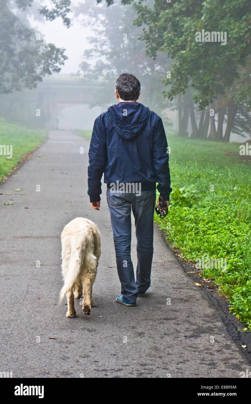 Uomo che cammina con il suo cane nella natura Immagini Stock