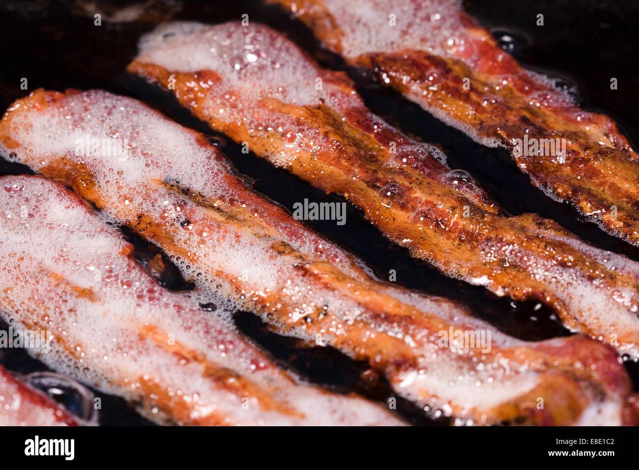 Grasso di pancetta eseguire il rendering di strisce di pancetta in una padella Immagini Stock