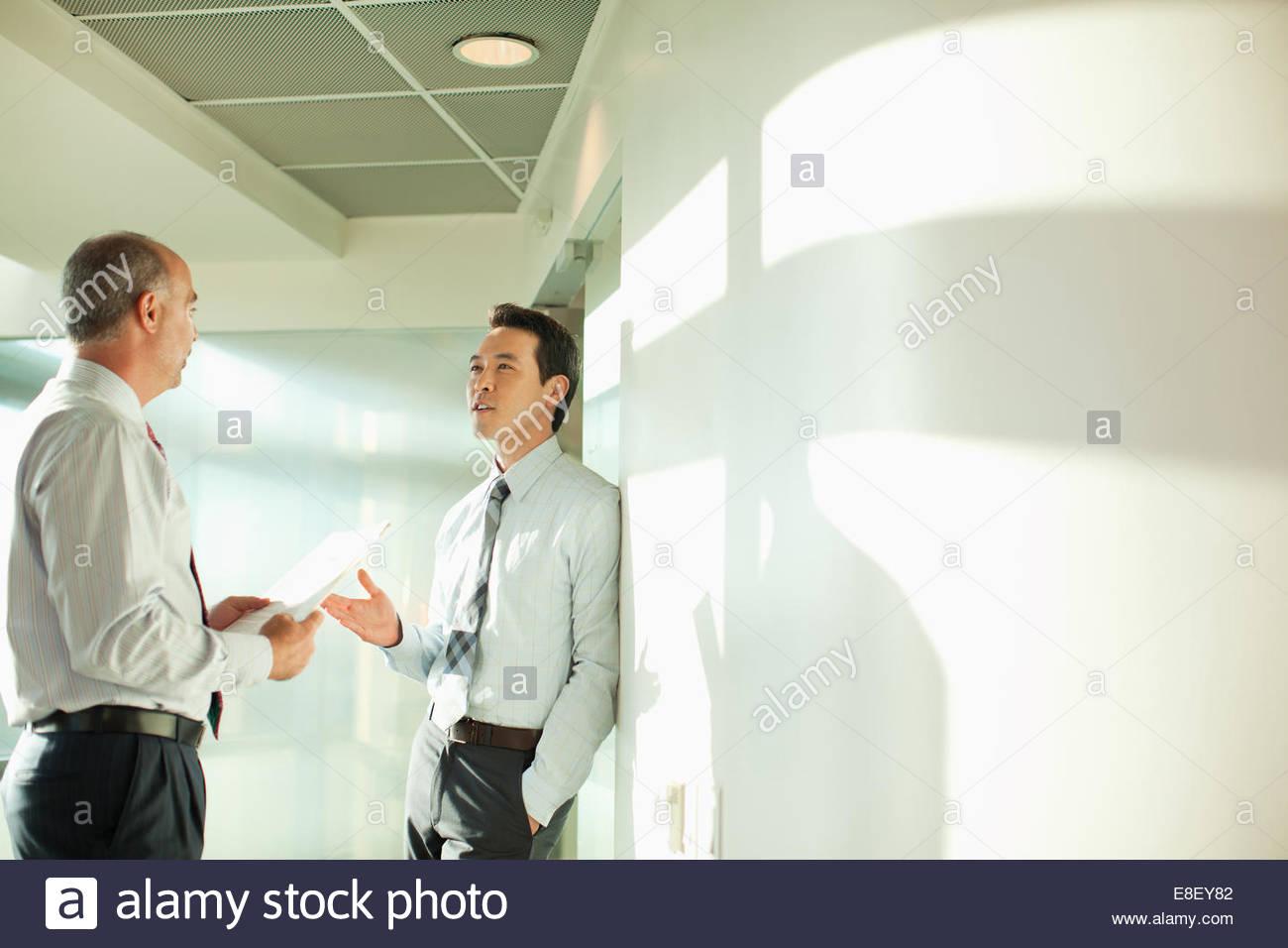 Imprenditori sorridente parlando in ufficio Immagini Stock