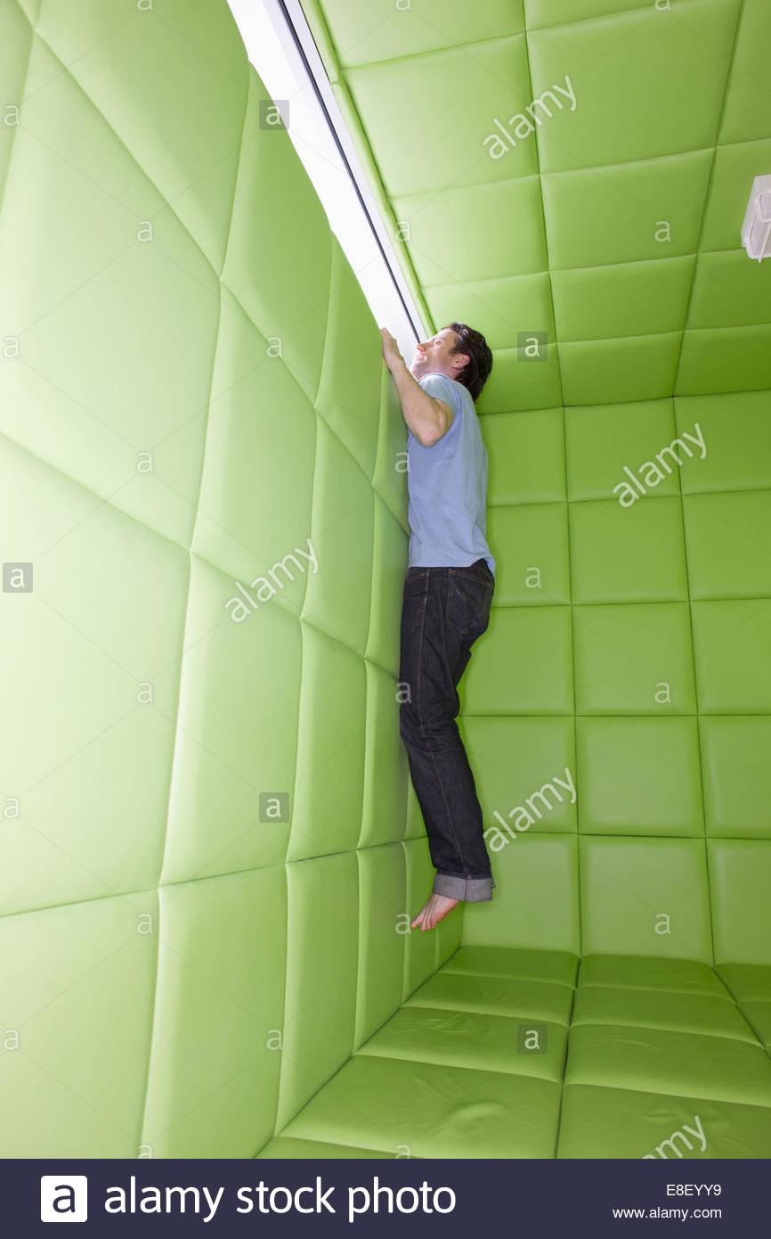 Uomo di raggiungere guardare dalla finestra in camera imbottita Immagini Stock