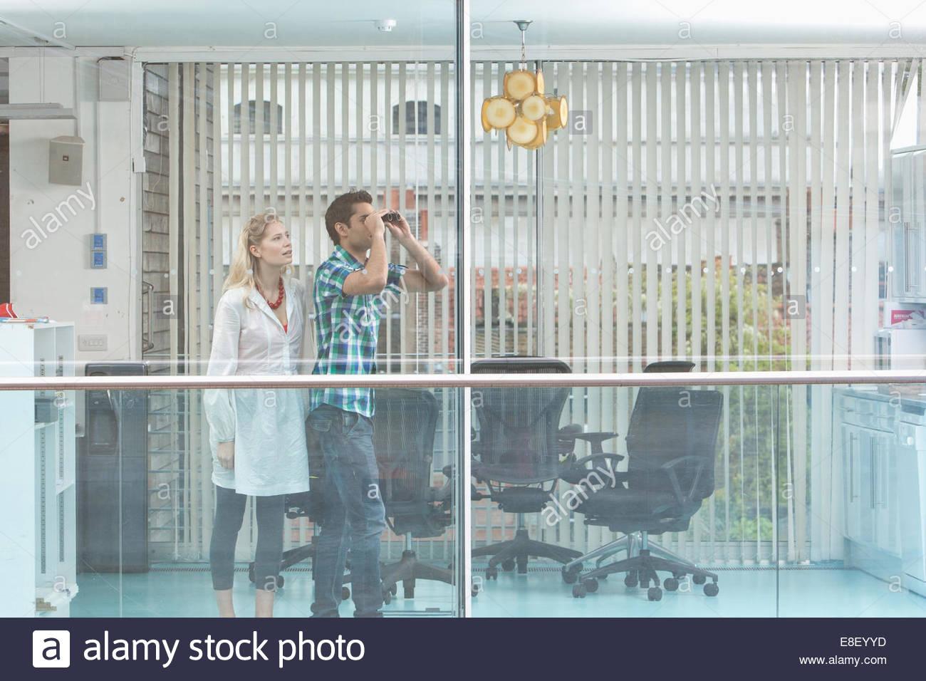 Uomo sorridente e la donna a guardare fuori dalla finestra Immagini Stock