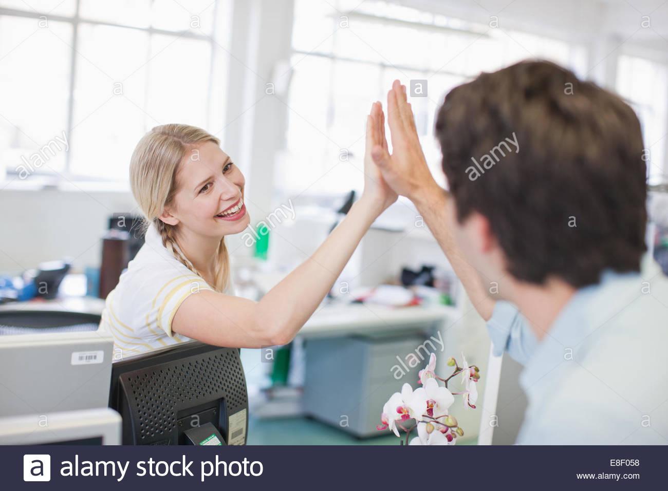 La gente di affari dando alta cinque in ufficio Immagini Stock