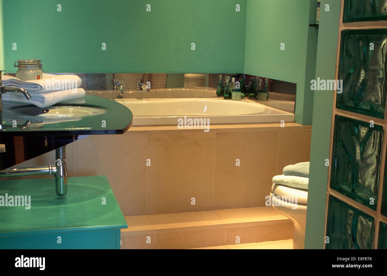 Asciugamani sul bacino di vetro nel verde moderno bagno con