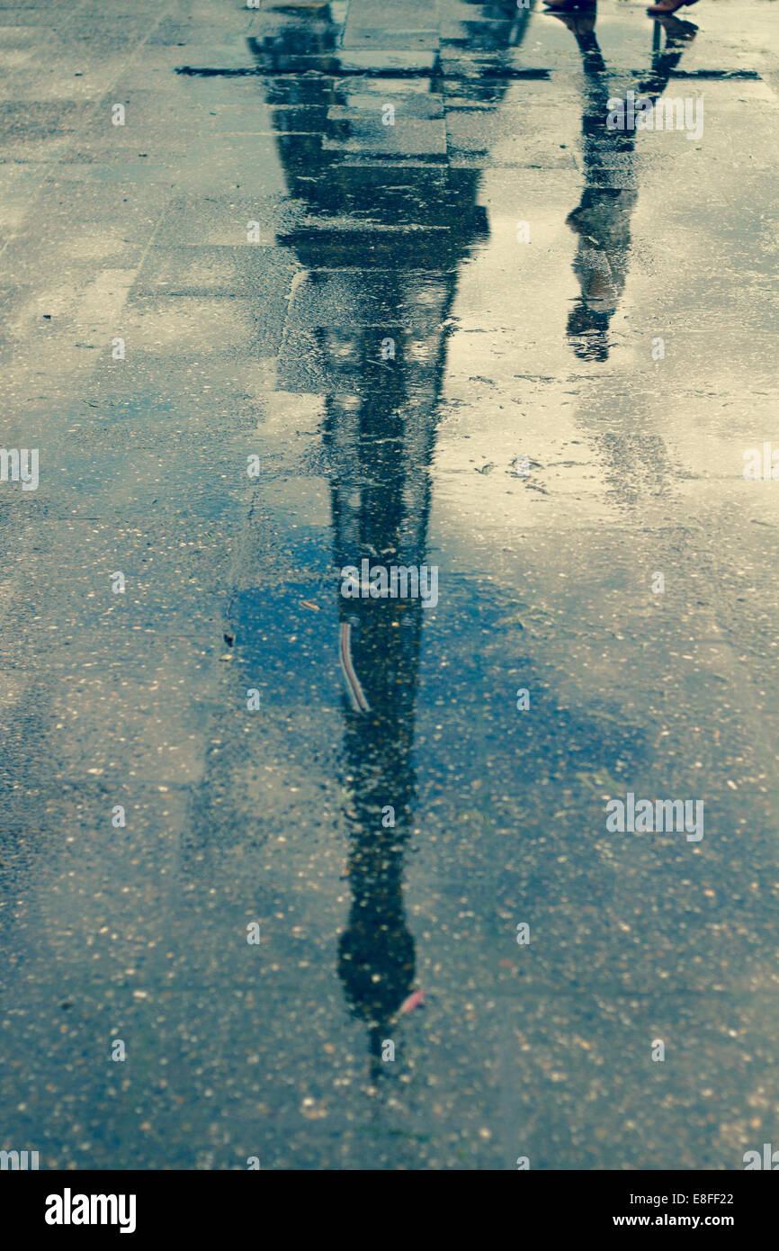 La riflessione di uomo passato a piedi la Torre Eiffel in una pozza, Parigi, Francia Immagini Stock