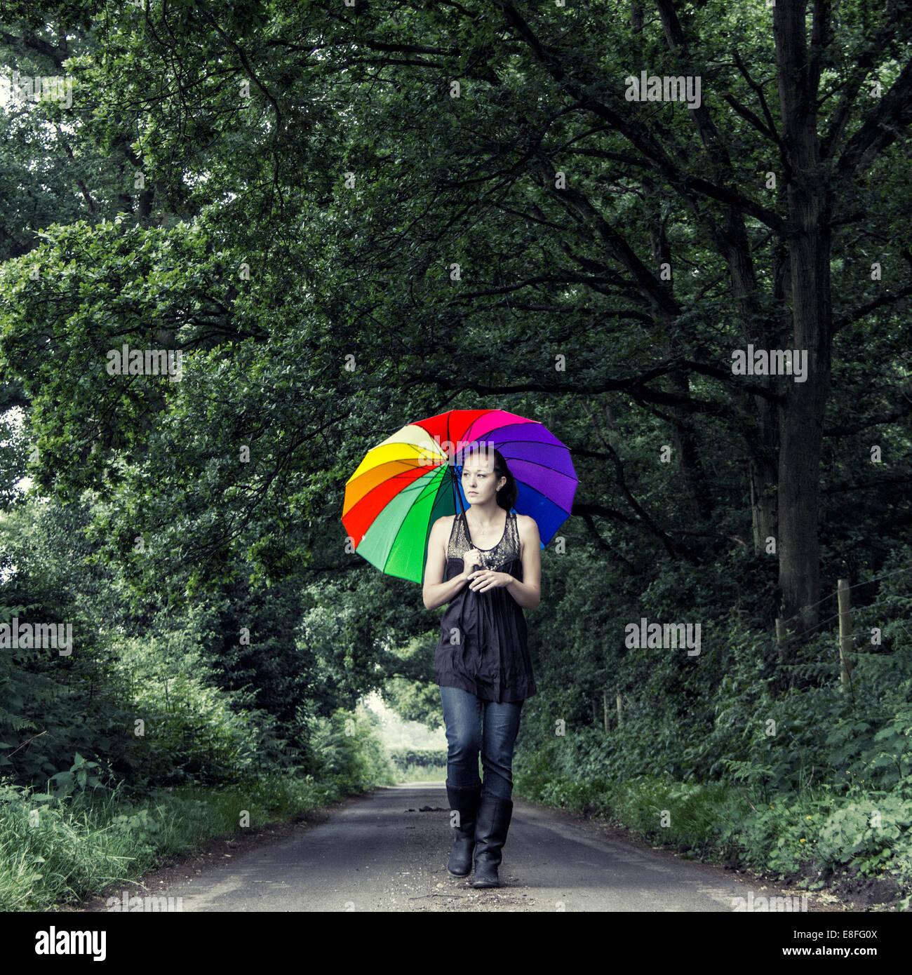 Donna camminare per strada con multi-ombrello colorato Immagini Stock