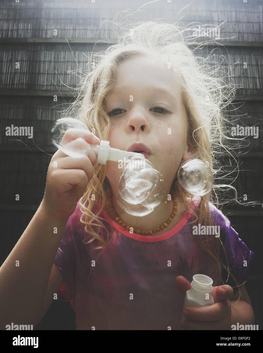 Ritratto di una ragazza soffia bolle di sapone Foto Stock
