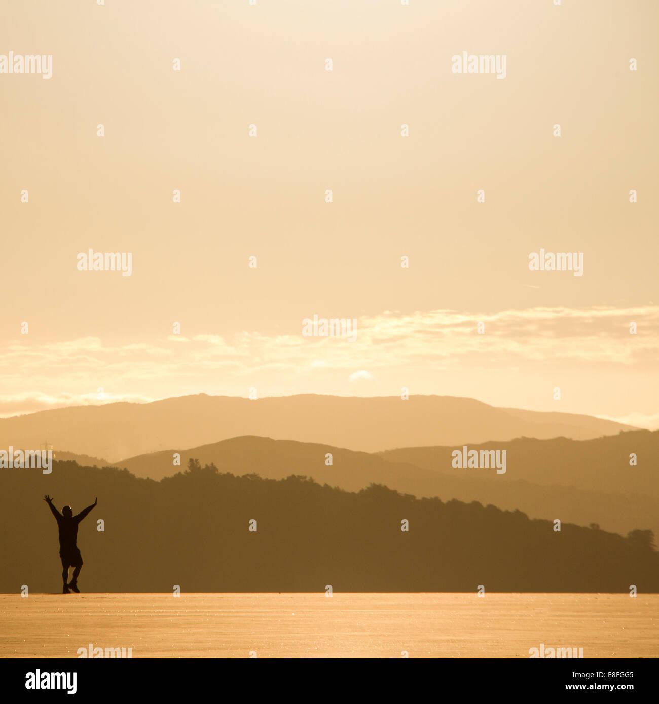 Silhouette di uomo nel sole di mattina e la vista del paesaggio Immagini Stock