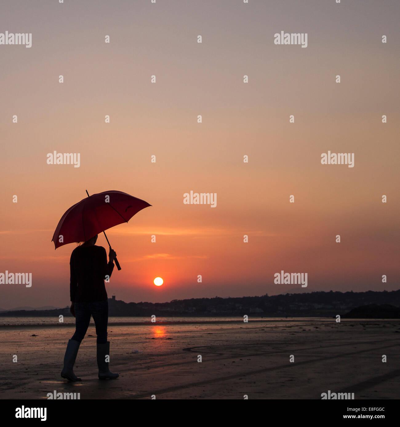 Chi si sveglia con ombrellone sulla spiaggia al tramonto Immagini Stock