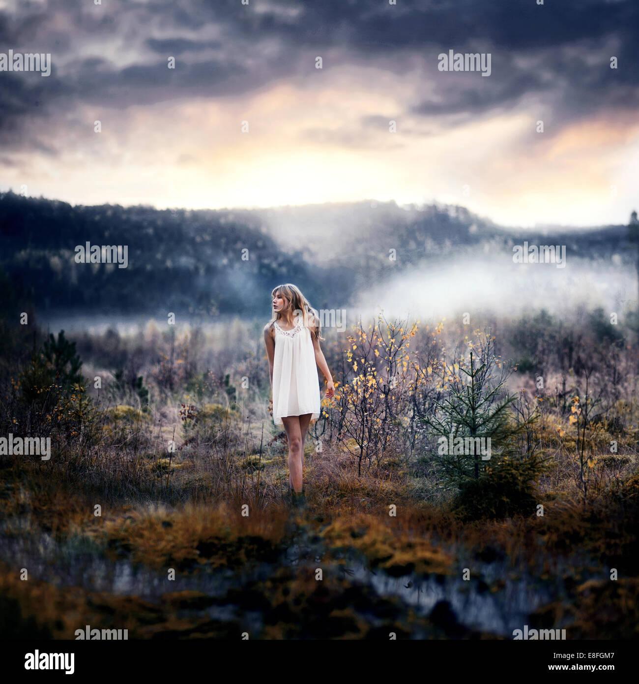 Donna in piedi nel paesaggio rurale Immagini Stock