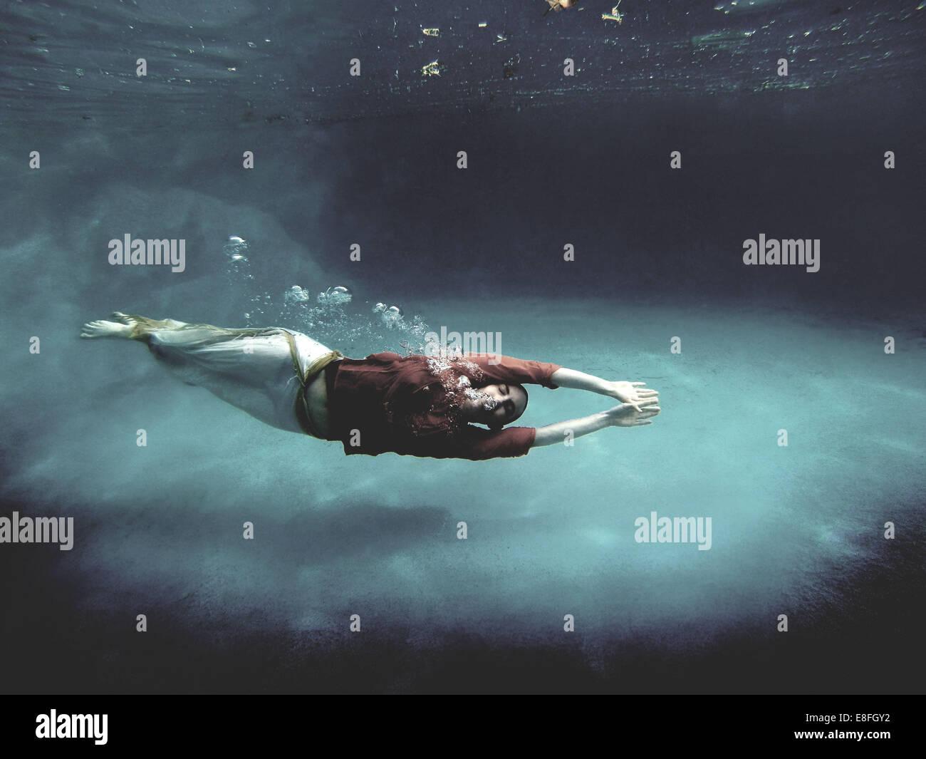 Donna nuoto completamente vestito underwater Immagini Stock
