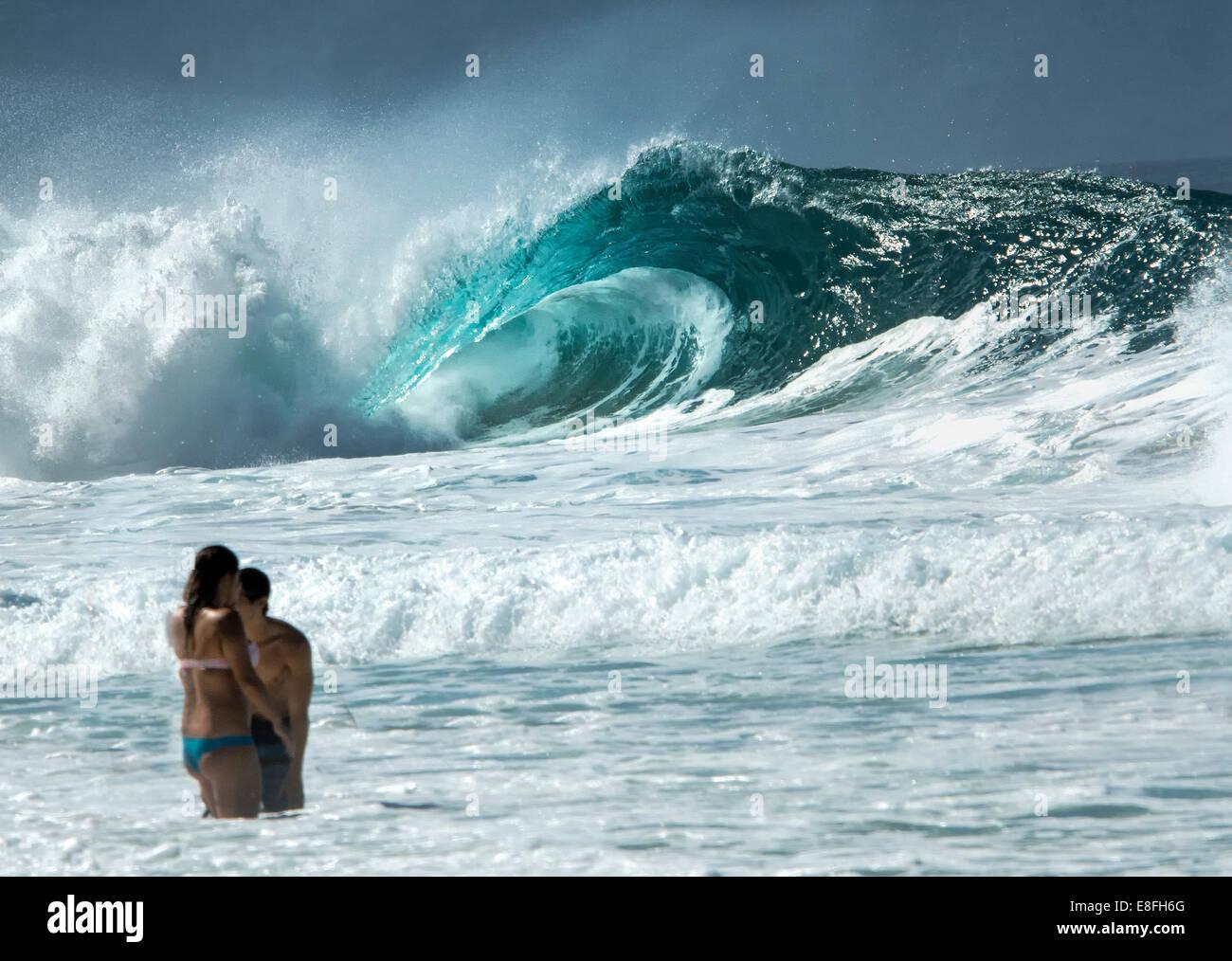 Le persone in piedi in oceano e oceano enorme ondata in background Immagini Stock
