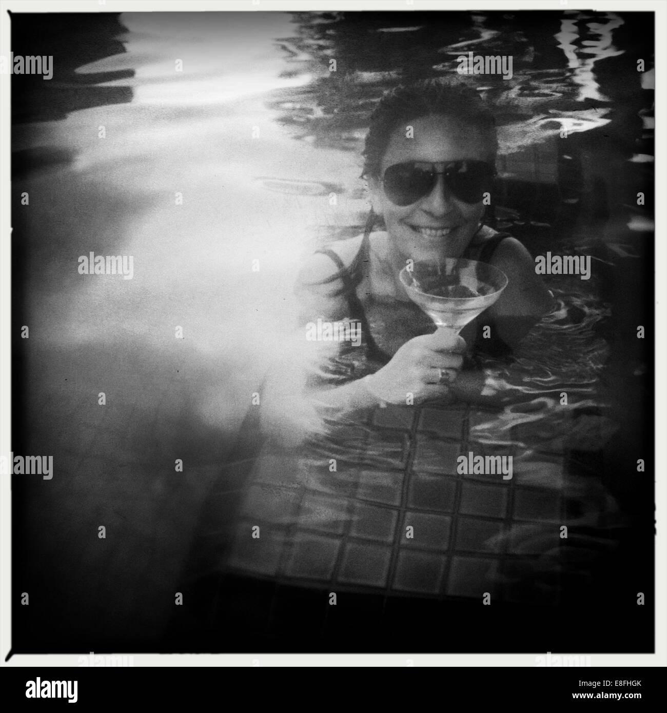 Donna di bere cocktail in piscina Immagini Stock