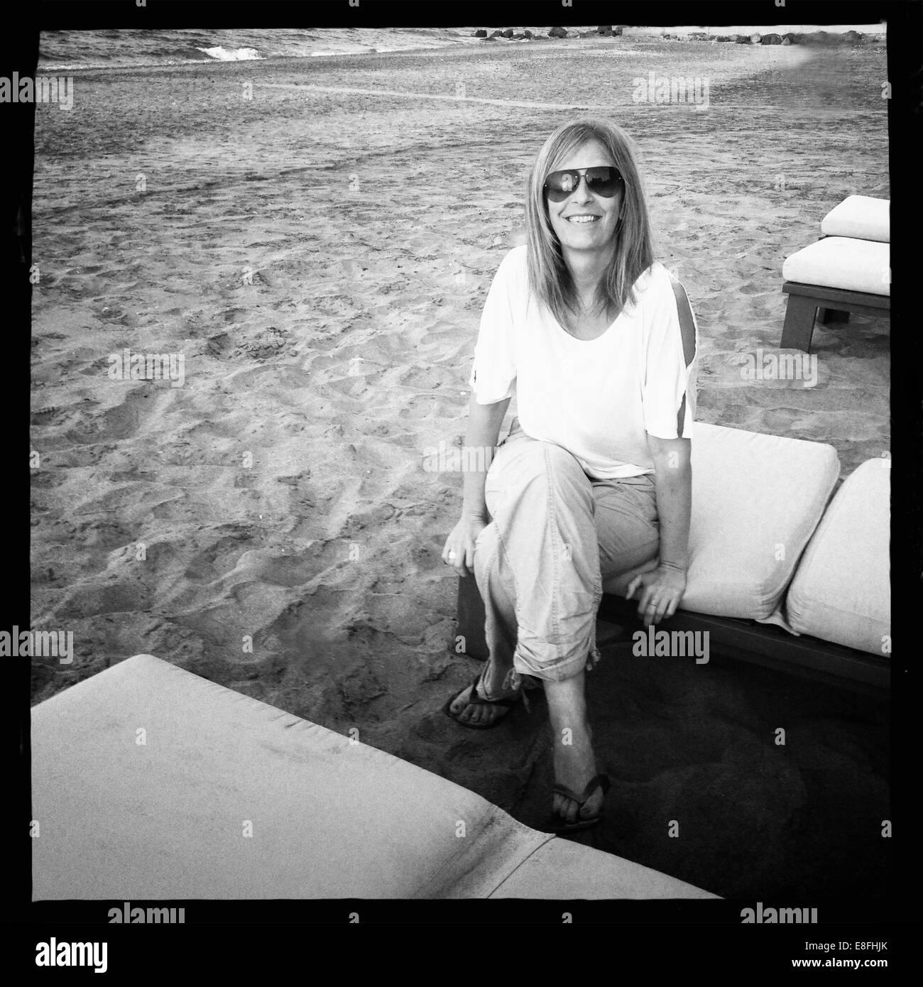 Donna sorridente seduta su un lettino sulla spiaggia, Muscat, Oman Foto Stock