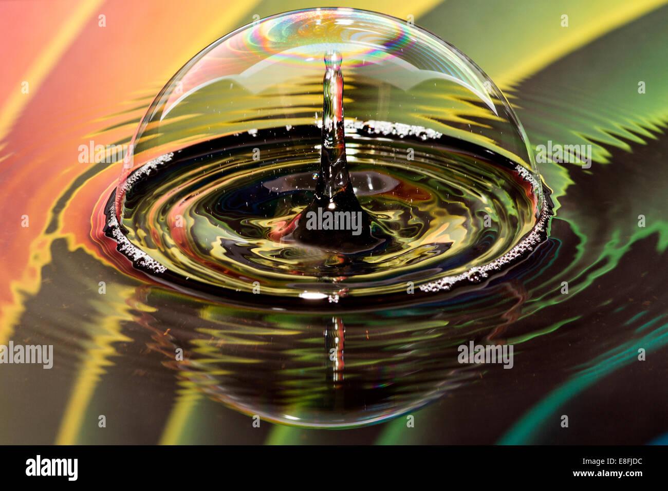 Gocce d'acqua sulla bolla con sfondo arcobaleno Immagini Stock