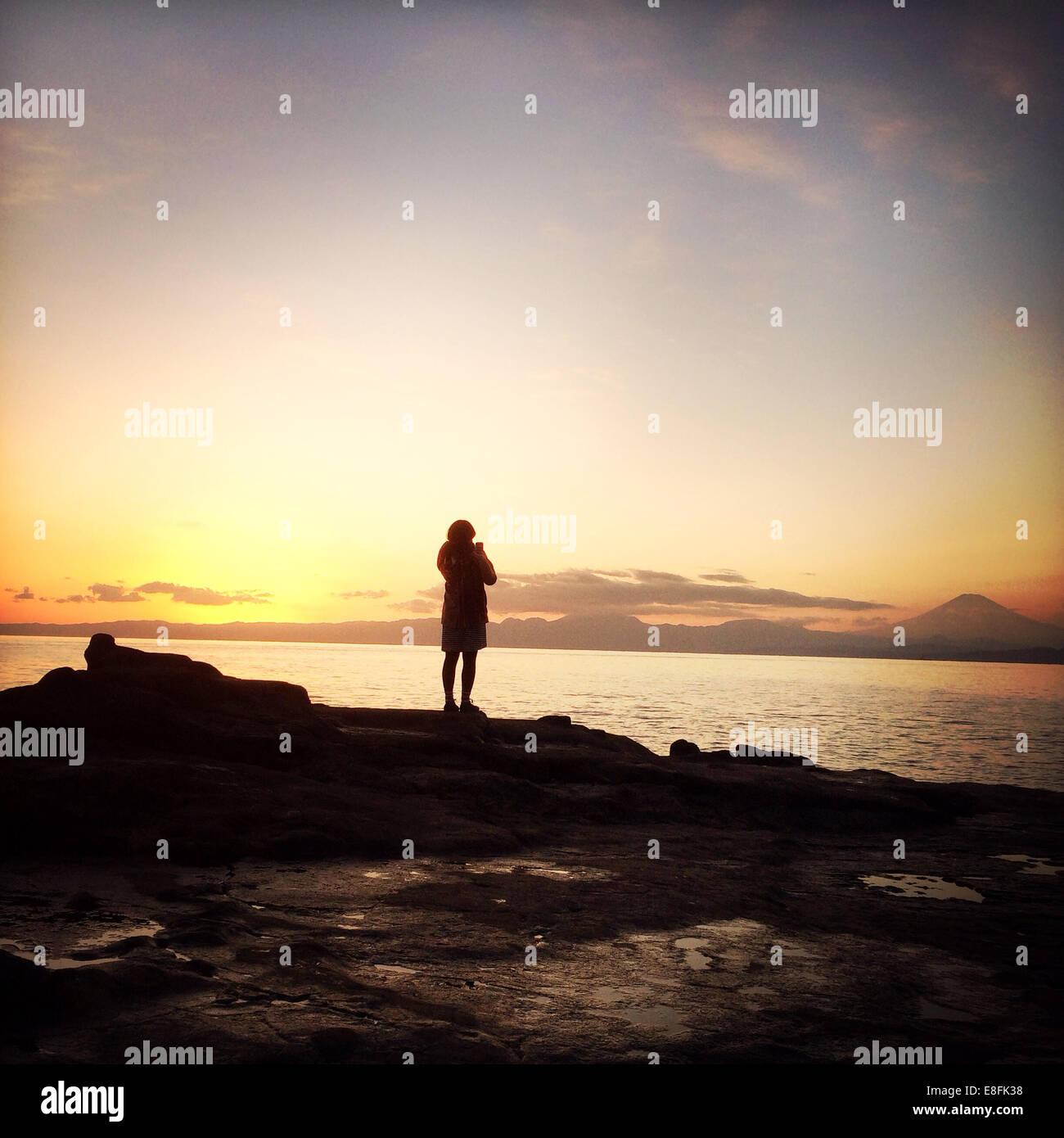 Vista posteriore di una donna in piedi sul mare Foto Stock