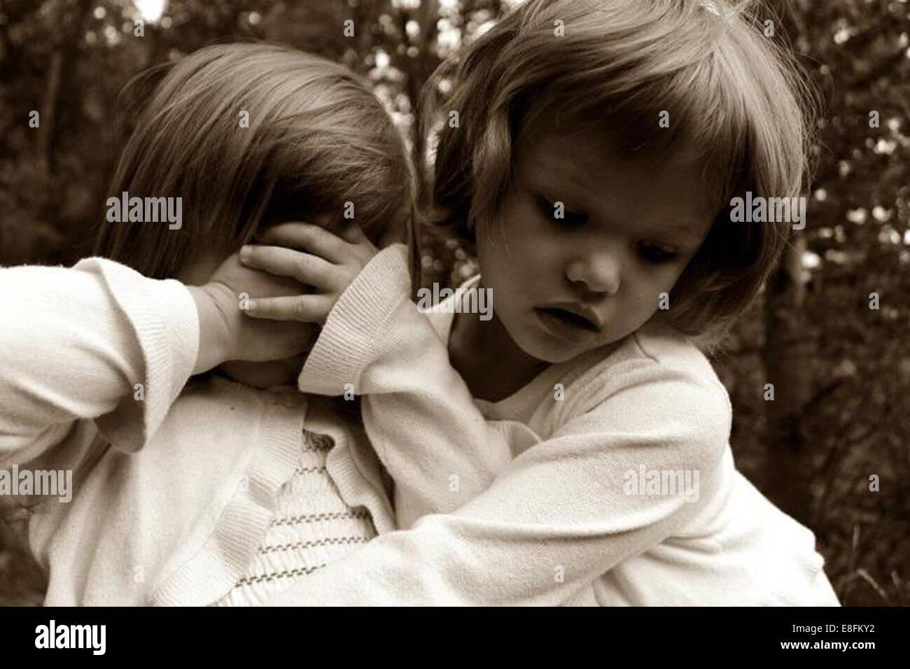 Due ragazze abbracciando all'aperto Immagini Stock