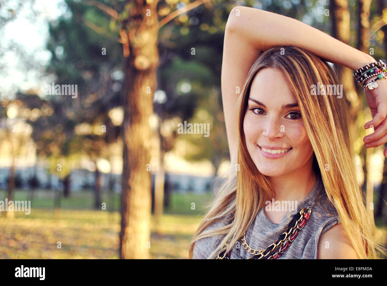 Ritratto di sorridente giovane donna in piedi in un parco Foto Stock