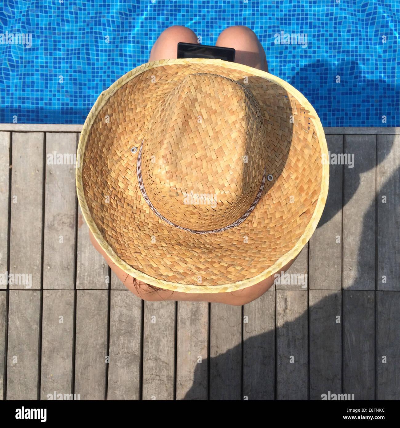 Vista aerea della donna con tavoletta digitale seduta sul bordo della piscina Immagini Stock