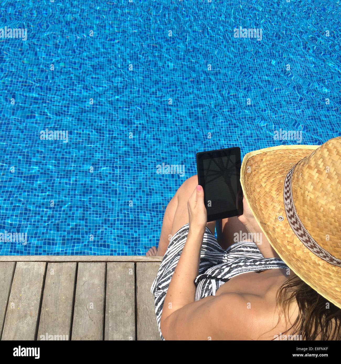 Donna con tavoletta digitale seduta sul bordo della piscina Immagini Stock