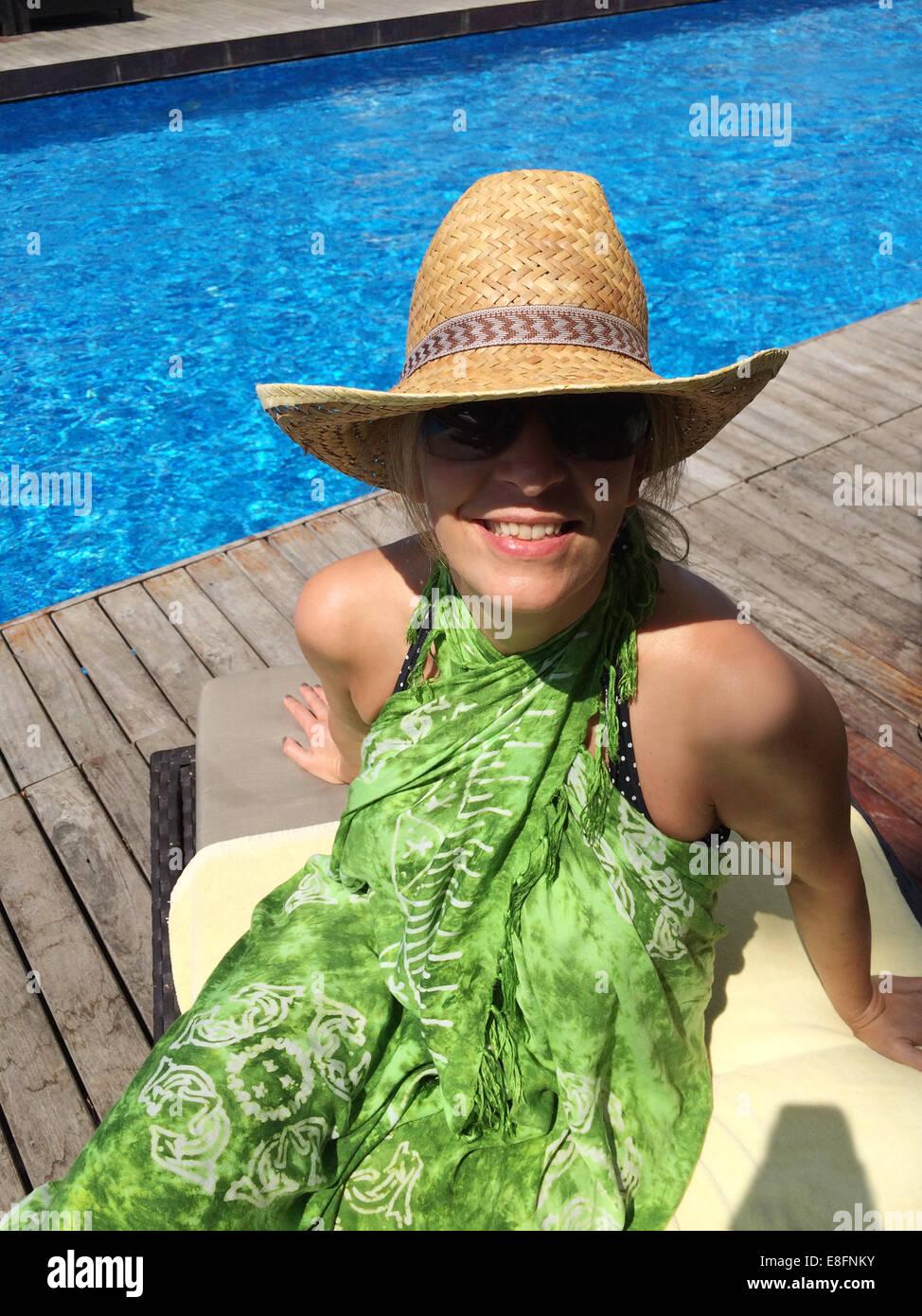 Donna sorridente seduto sulla sedia a sdraio da piscina Immagini Stock