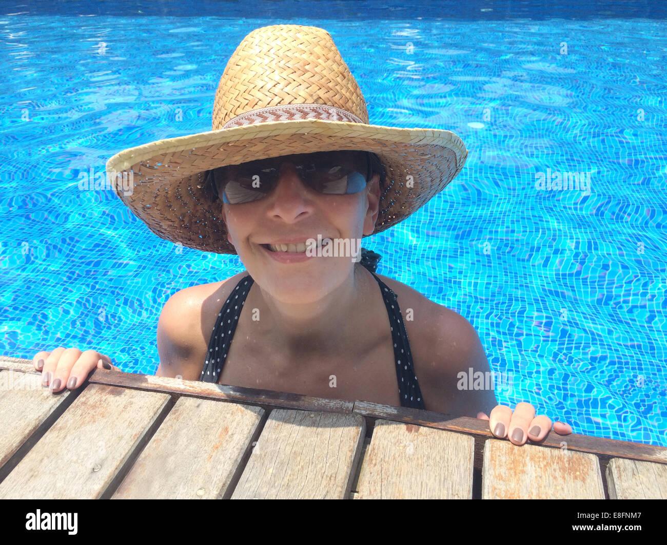 Donna sorridente in piscina, indossare un cappello di paglia Immagini Stock