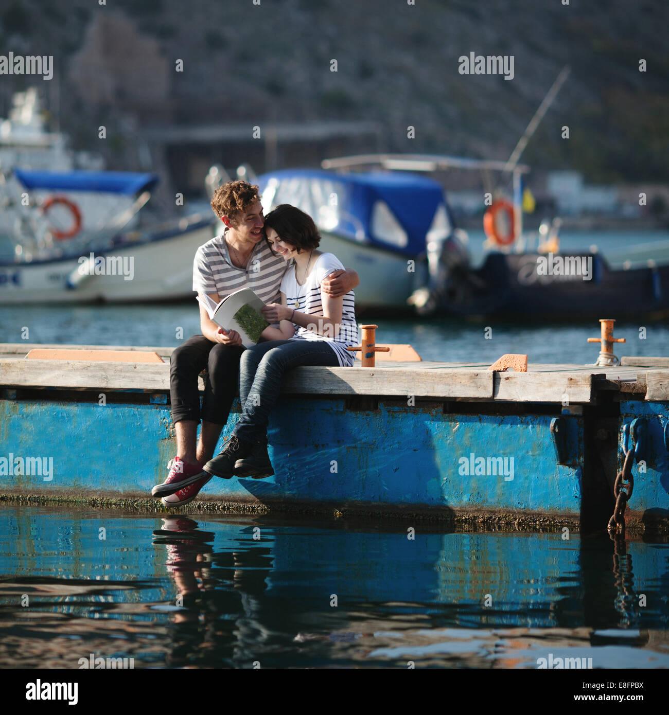 Coppia adolescenti (14-15) seduto sul molo, abbracciando Immagini Stock