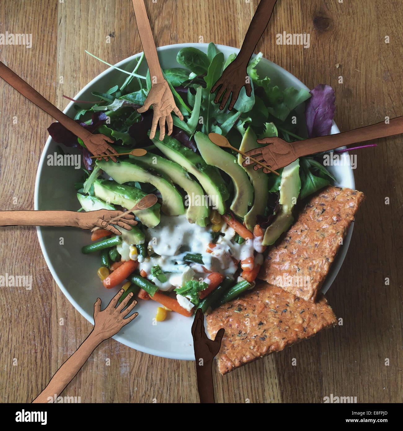Le mani umane afferrando una sana insalata Immagini Stock