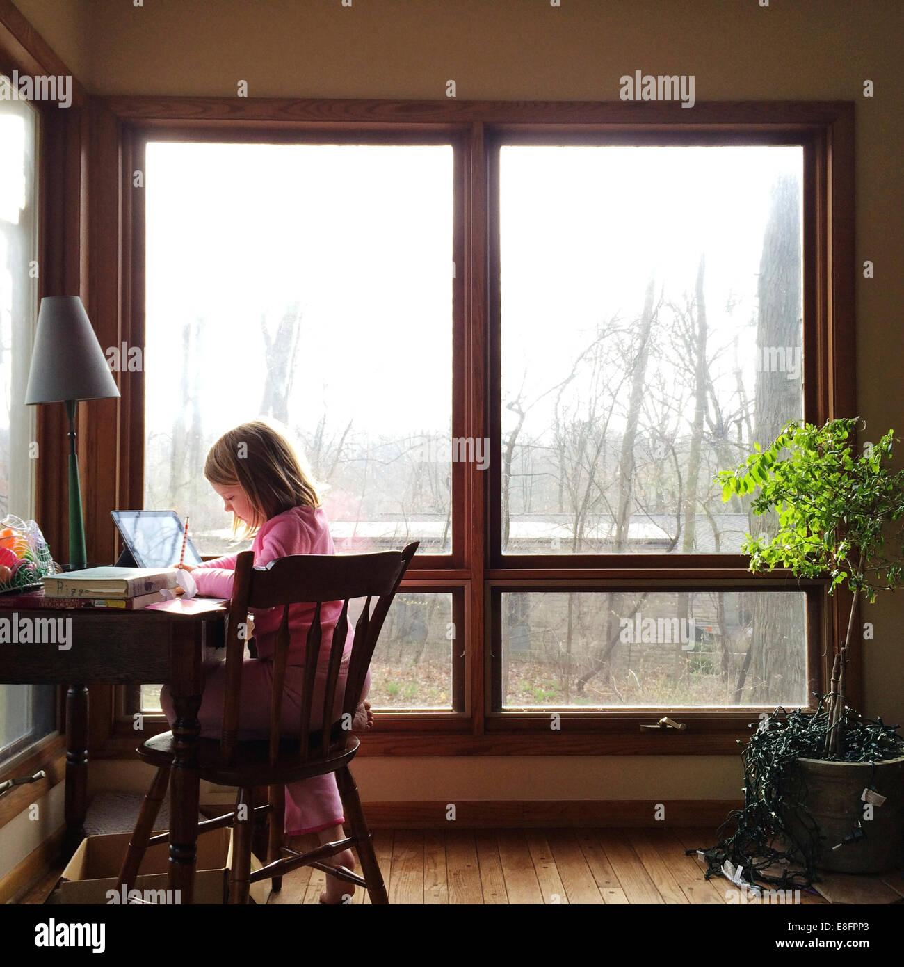 Ragazza seduta alla sua scrivania studiando Immagini Stock