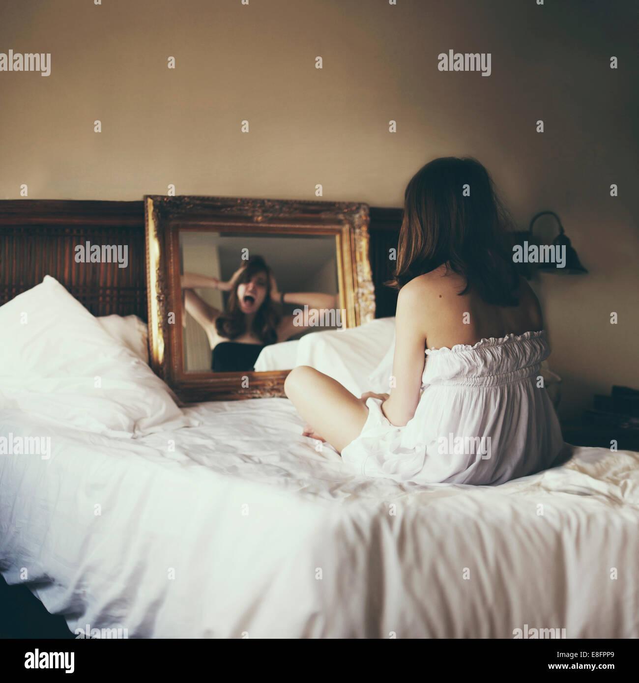 Donna seduta sul letto cercando in specchio con una riflessione urlante Immagini Stock