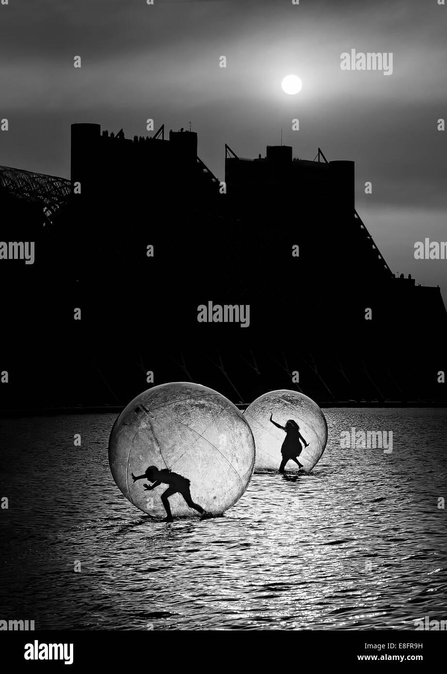 Silhouette di due bambini acqua di calpestio in sfere trasparenti Immagini Stock