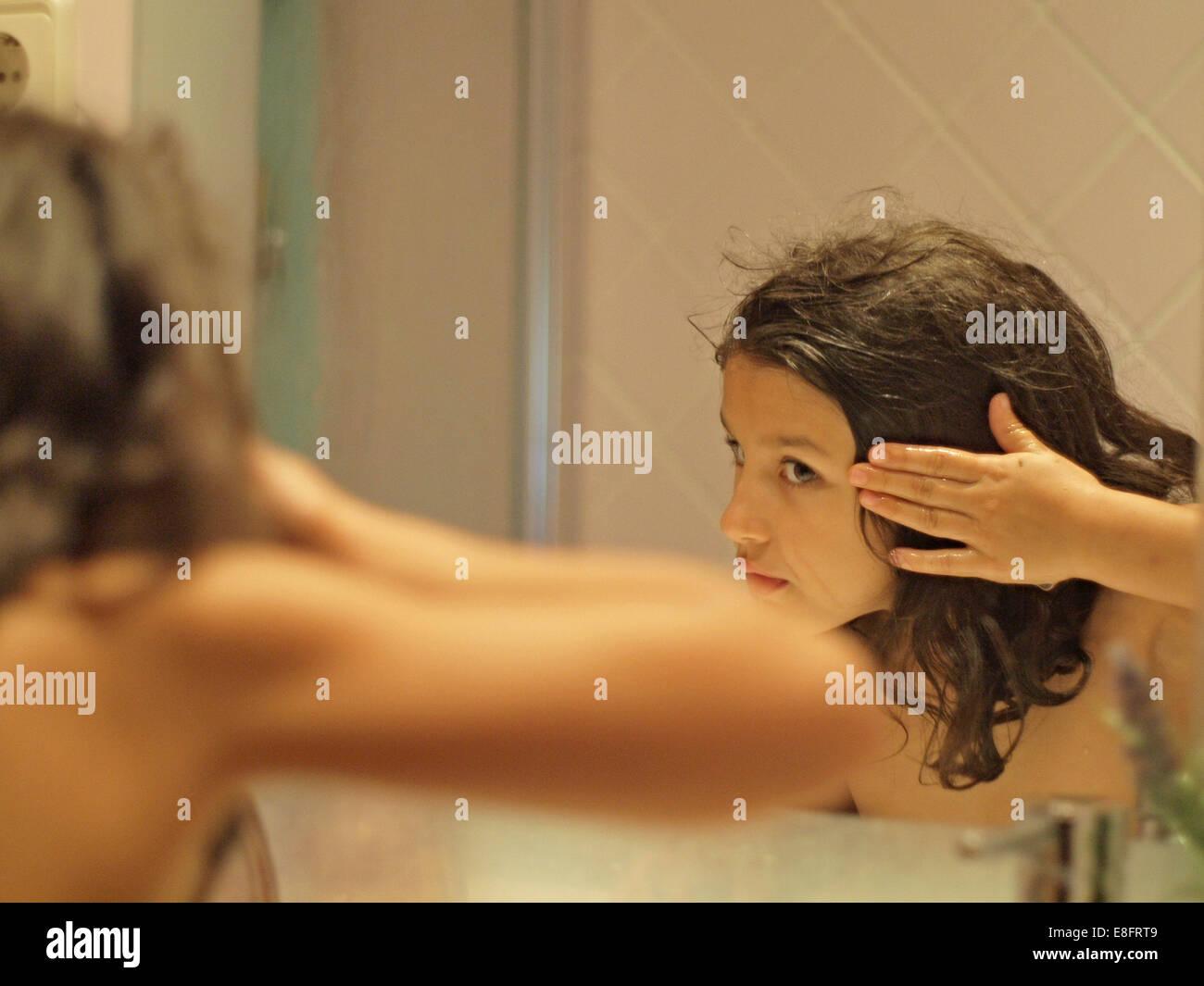 La ragazza con i capelli umidi guardando il riflesso dello specchio Immagini Stock