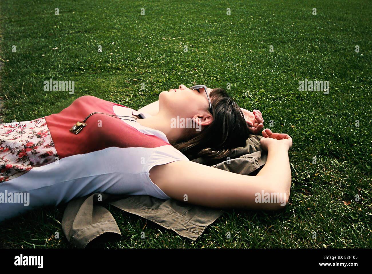 Donna sdraiata su erba rilassante Immagini Stock