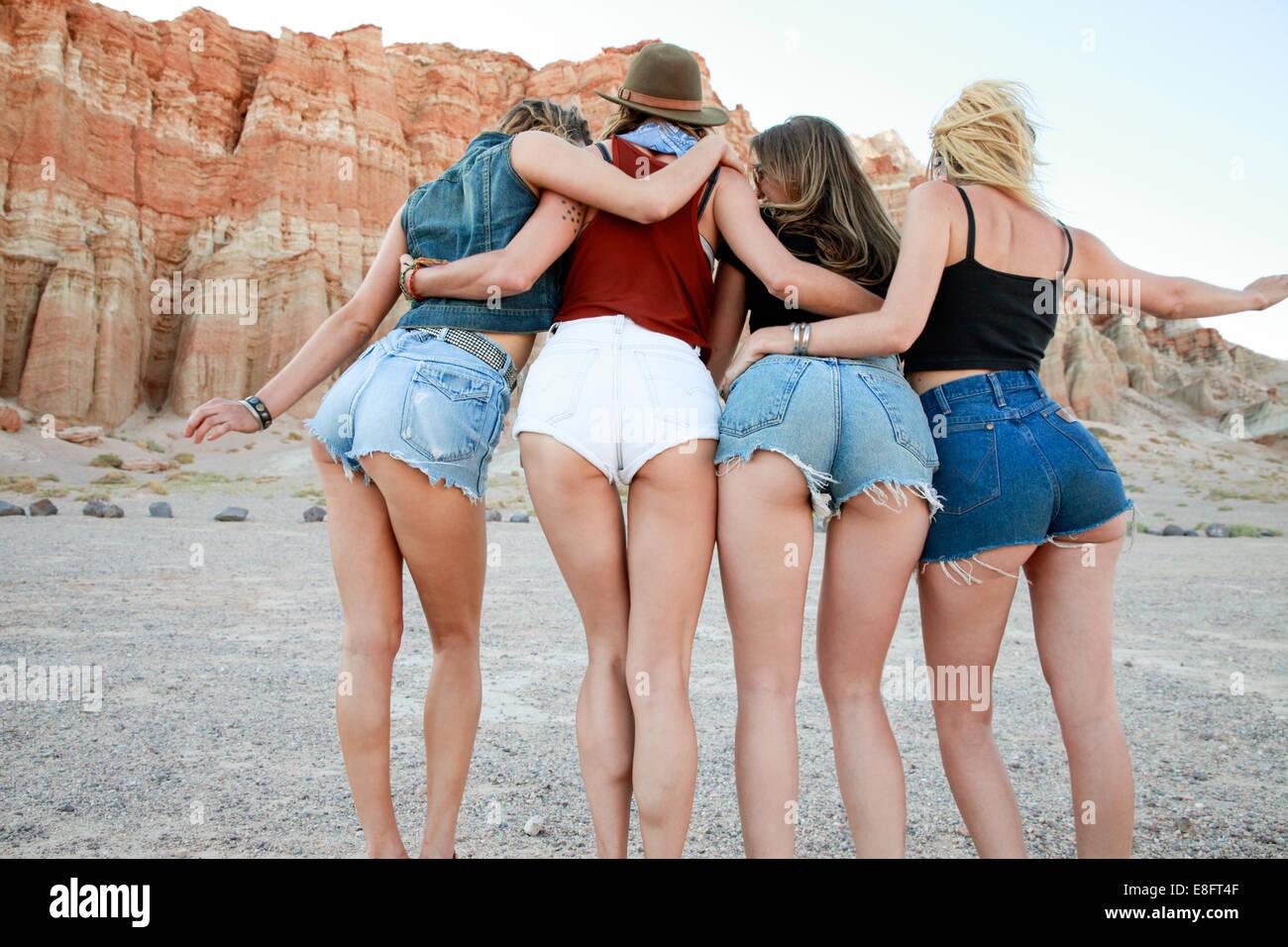 Vista posteriore di quattro donne che indossano pantaloncini denim Immagini Stock