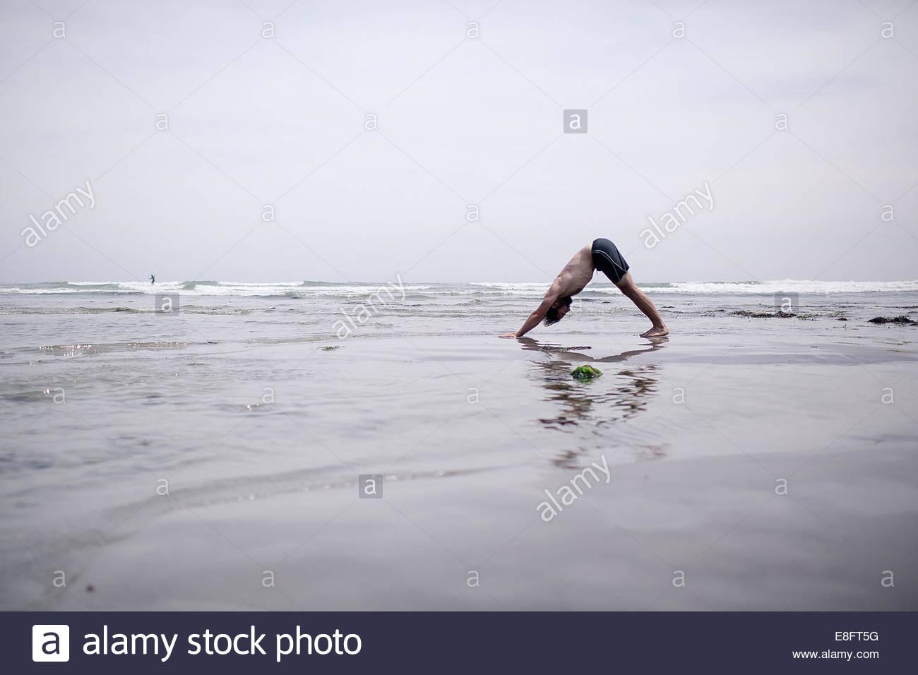 Uomo che fa del cane verso il basso lo yoga pone sulla spiaggia Immagini Stock
