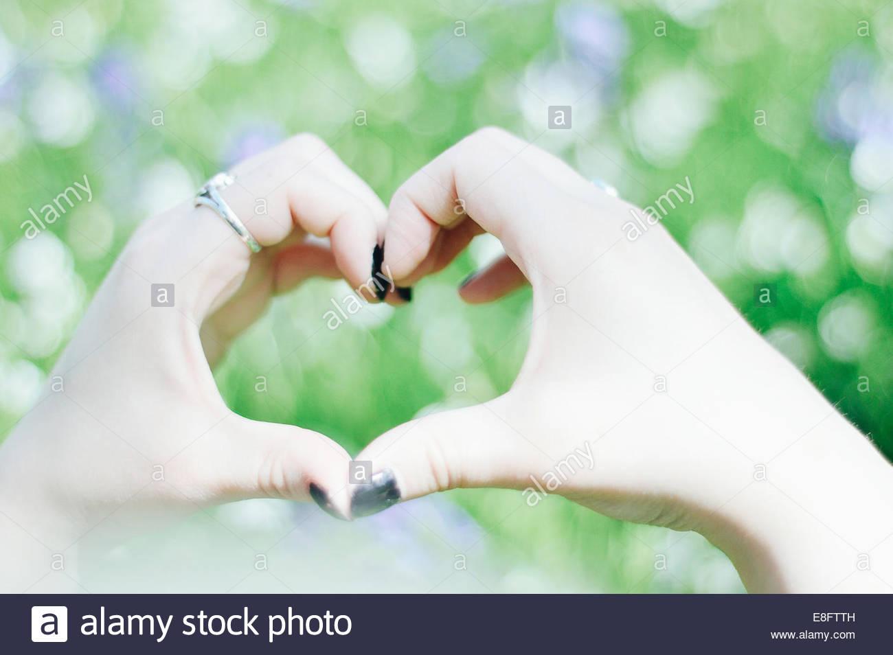 Donna messa a forma di cuore con le mani Immagini Stock