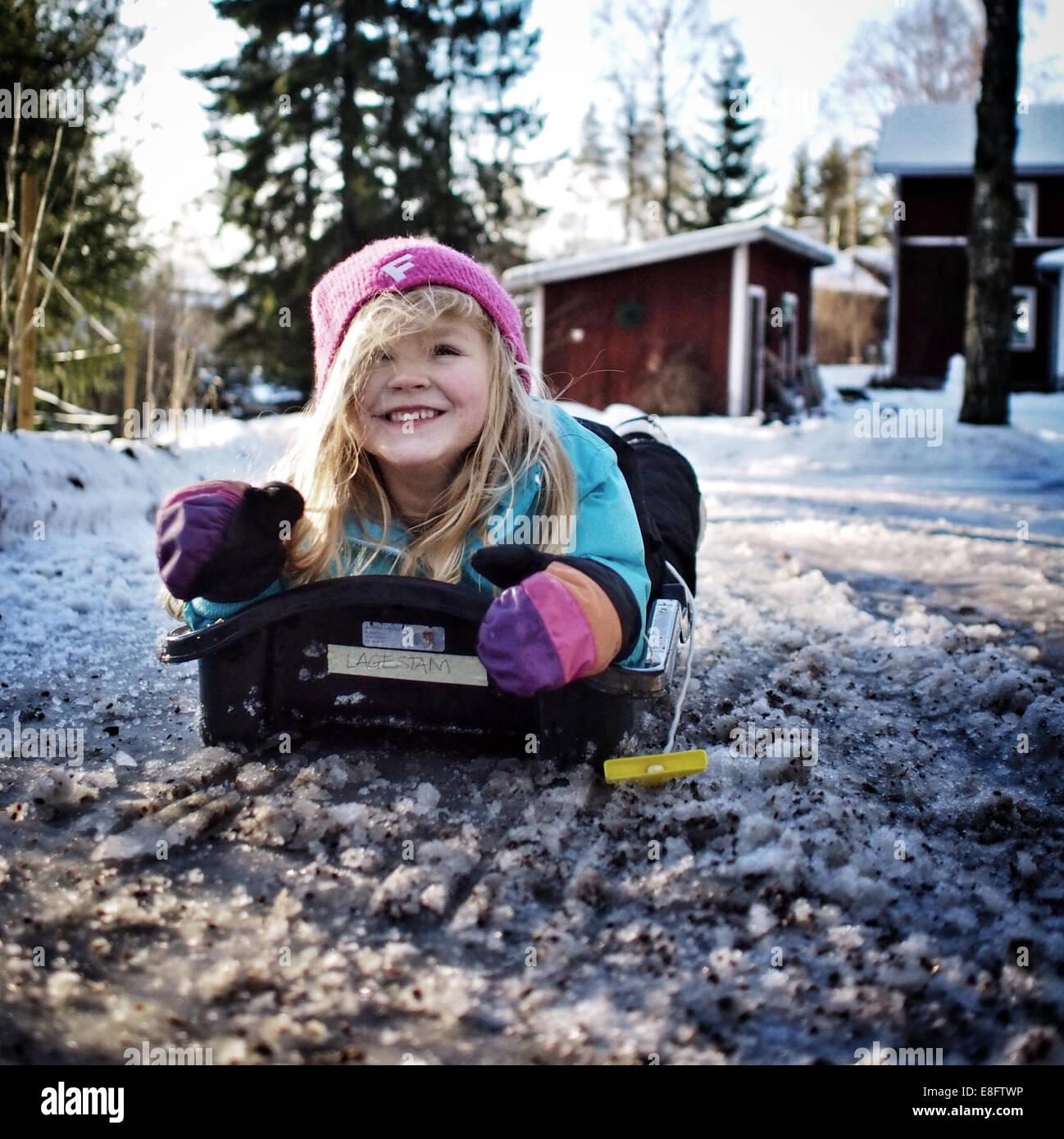 La Svezia, ragazza (6-7 anni) giacente su slitta Immagini Stock