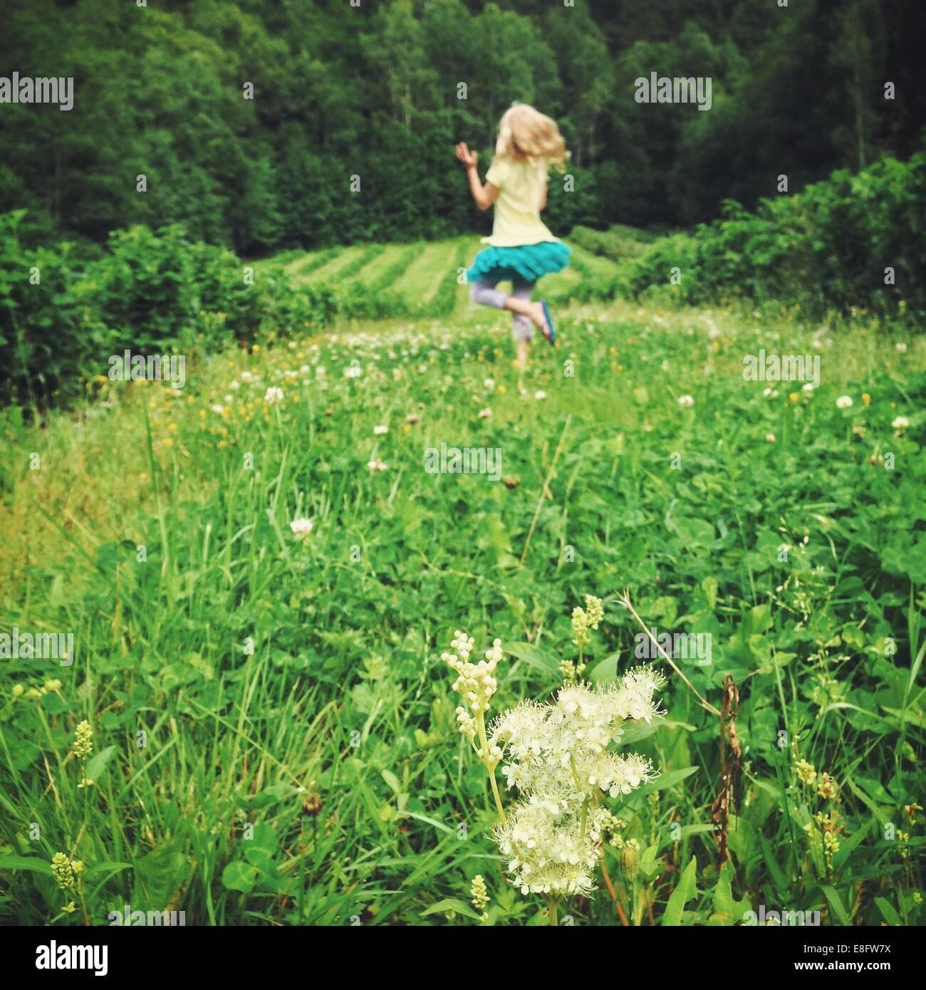 La ragazza (12-13) di saltare sul prato Immagini Stock