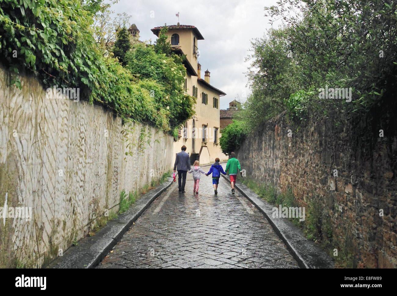 L'Italia, Toscana, Firenze, padre di tre bambini (10-11, 12-13) camminando sul giorno di pioggia Immagini Stock