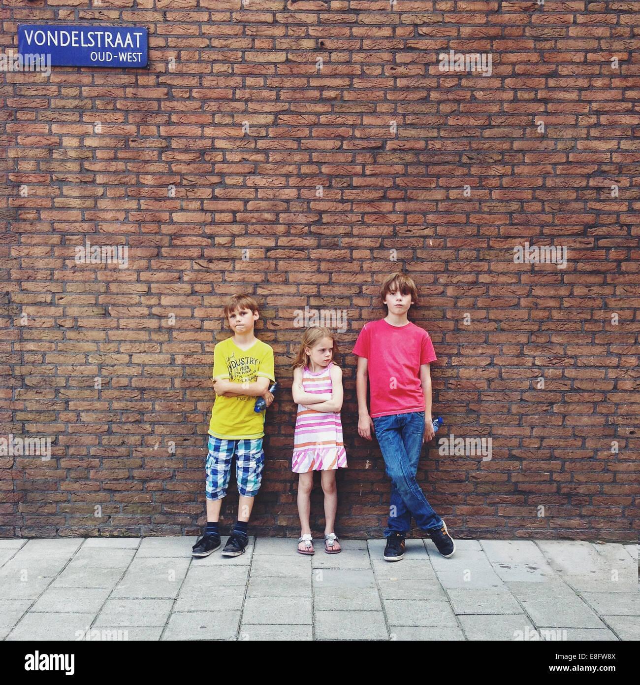 Tre bambini (10-11, 12-13) in piedi di fronte a un muro di mattoni Immagini Stock