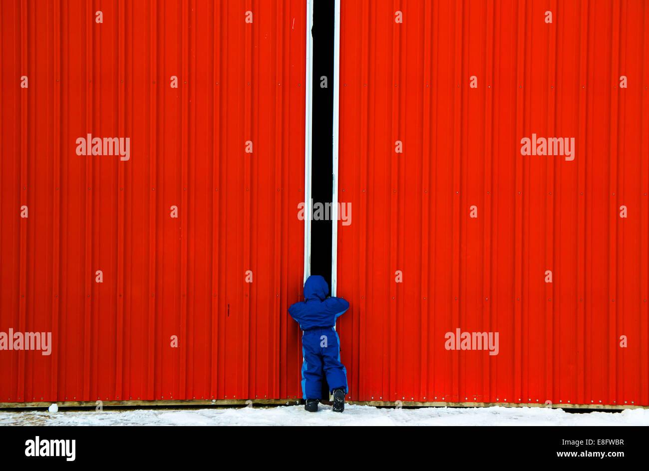 Ragazzo che guarda attraverso lo spazio in porte (4-5 anni) Immagini Stock