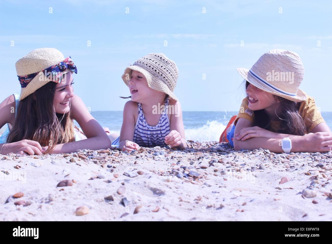 Le tre ragazze sulla spiaggia che giace sulla loro parte anteriore Immagini Stock