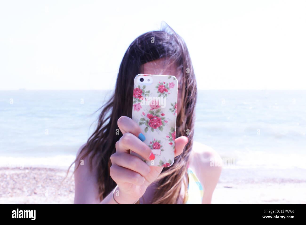 Ragazza di prendere foto con il suo telefono cellulare Immagini Stock