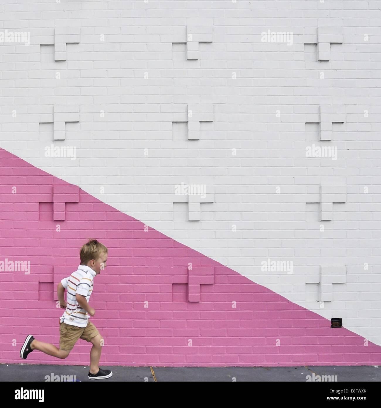Ragazzo in esecuzione passato rosa e muro bianco Immagini Stock