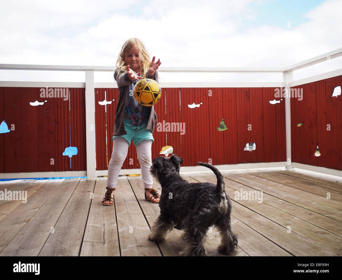Ragazza giovane (6-7 anni) giocando con il cane Immagini Stock