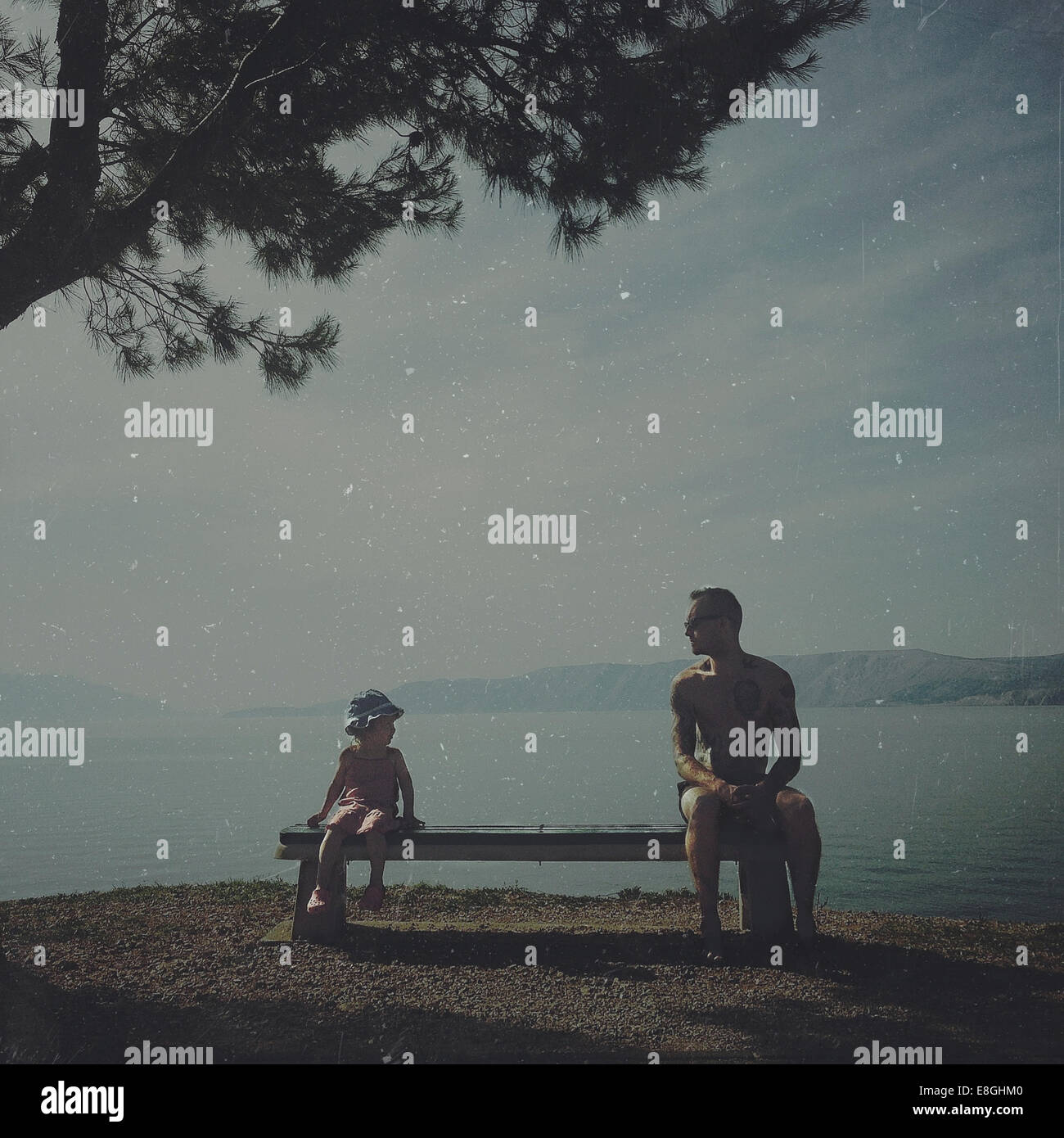 Croazia, padre e figlia (2-3) seduta sul banco da mare Immagini Stock