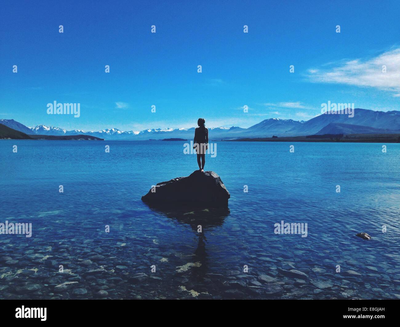 Donna in piedi su una roccia, Lago Tekapo, Canterbury, Nuova Zelanda Immagini Stock