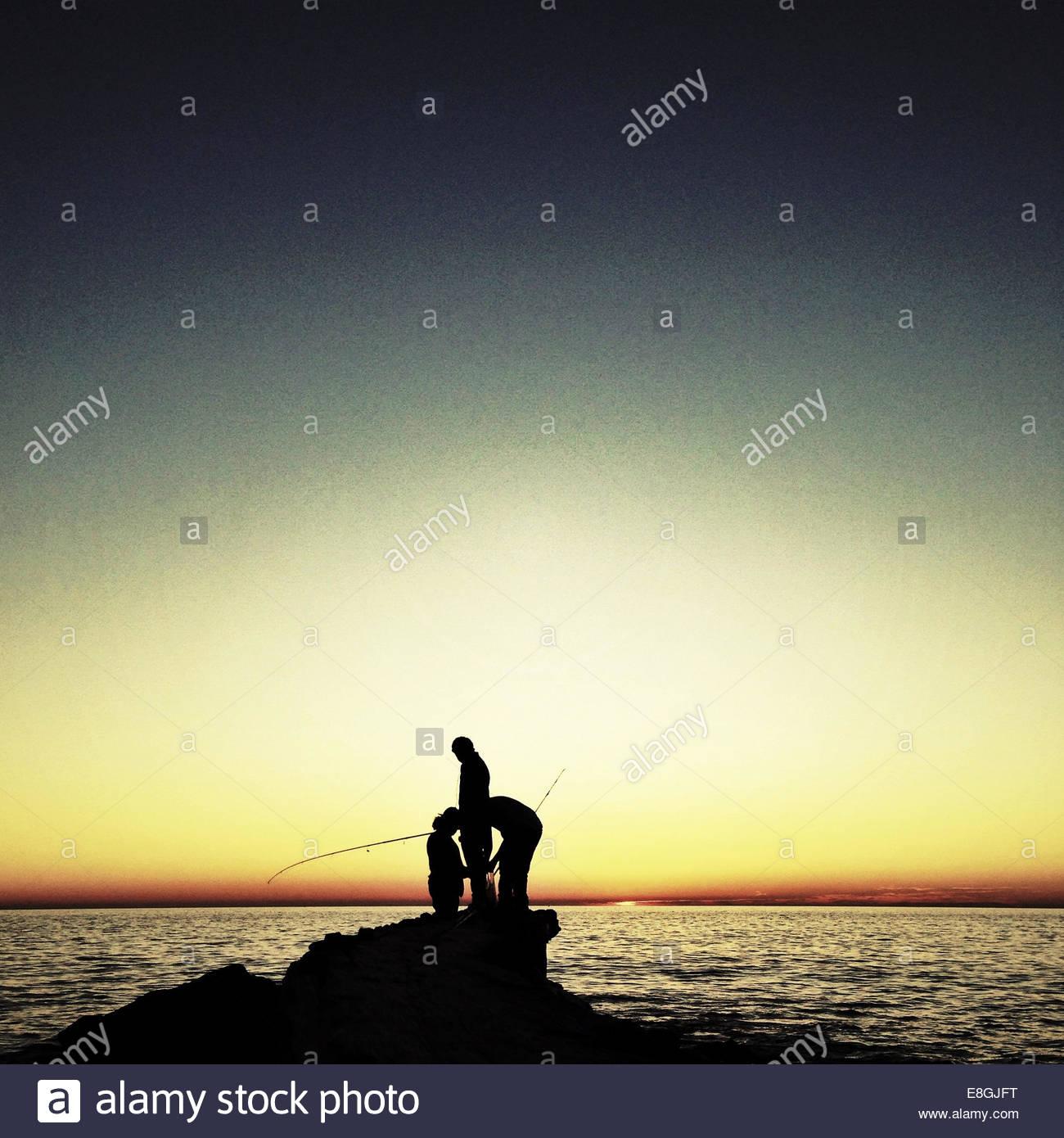 Silhouette di uomini la pesca Immagini Stock